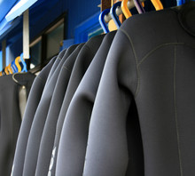 A Row Of Wetsuits Hanging Up T...