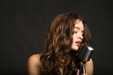 Fototapeta Beautiful sexy young woman singing