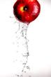 Leinwandbild Motiv Water pouring  and splashing over a red delicious apple on white