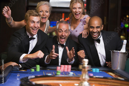 Fotografie, Obraz  Five people in casino playing roulette smiling