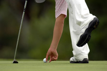 A Young Male Golfer Picks Up H...