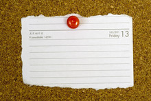 Piece Of Paper Showing The Date Friday 13 Pegged To A Cork Board