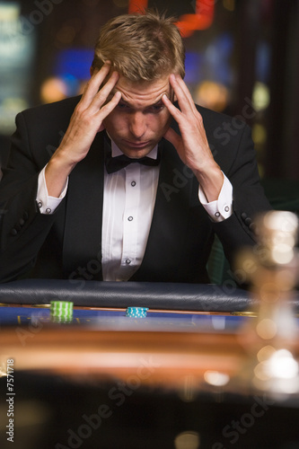 Man losing at roulette table плакат