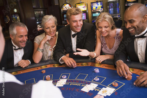 Fotografija  Group of friends playing blackjack in casino