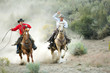 canvas print picture Two Cowboys galloping and roping through the desert