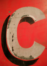 Letter C On Antique Tin Sign With Peeling Paint