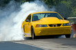 canvas print picture - Smoke from the tires of a yellow racer