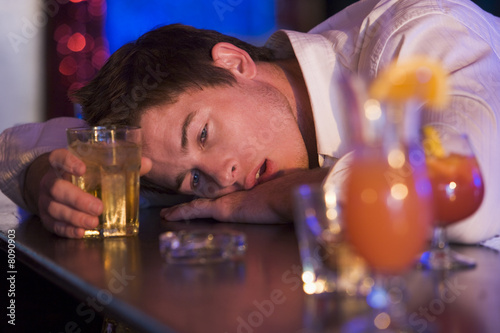 Fotografering  Drunk young man resting head on bar counter
