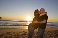 Pregnant Couple On The Beach At Sunset