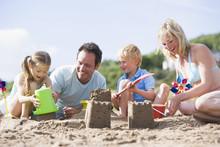 Family On Beach Making Sand Castles Smiling