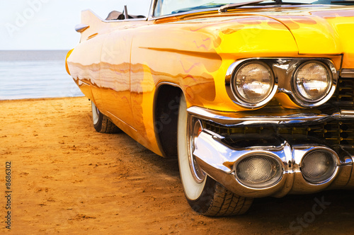 Fotografering Classic yellow flame painted Cadillac at beach