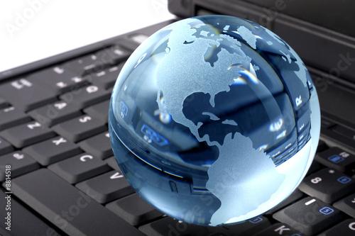 Aluminium Prints Scooter Blue glass globe on a laptop keyboard