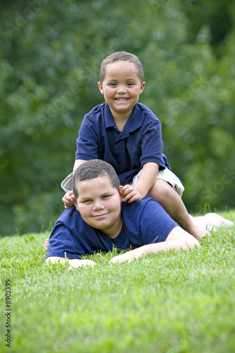 Fényképezés  Two brothers playing on fresh green grass