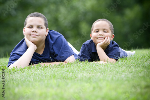 Valokuva  Two brothers lying on their fronts on fresh green grass