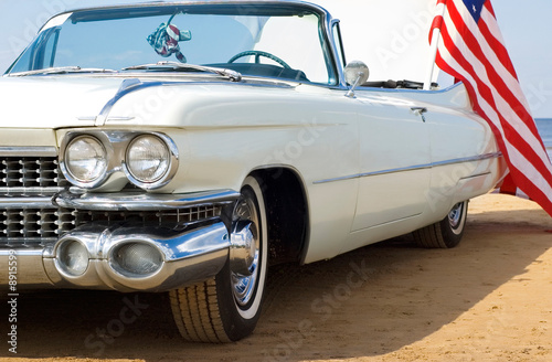 Keuken foto achterwand Oude auto s Classic white Cadillac at the beach with American flag