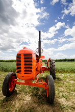 An Old Orange Retro Tractor In A Field