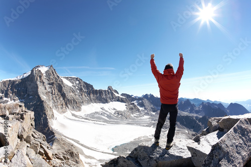 Fototapeta Sign of victory: climber on the top of the mountain obraz