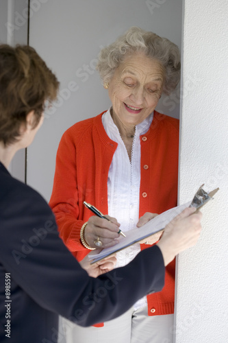 Photo  Attractive senior woman signing a document at her front door