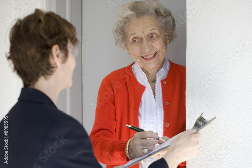 Valokuva  Attractive senior woman signing a document at front door