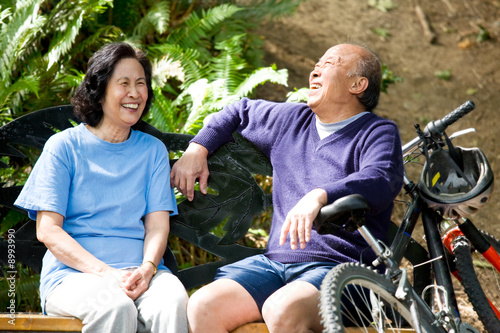 Fotografia  A shot of senior asian couple sitting on a bench at a park