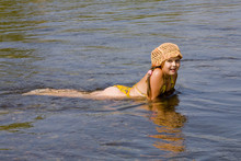 Little Girl In Orange Hat Swimming In A River In The Summer