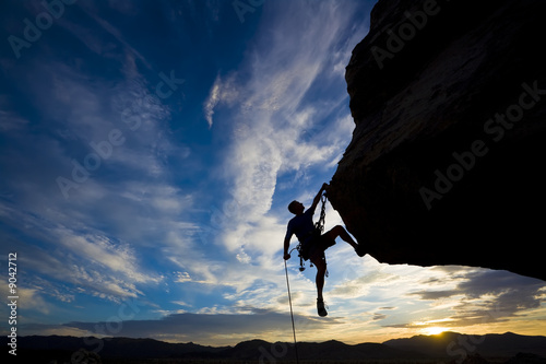 Fotografie, Obraz  Rock climber dangling from a cliff.