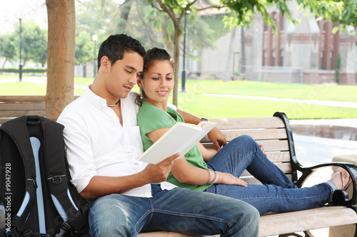Fotografie, Obraz  Attractive students at college sitting on bench reading