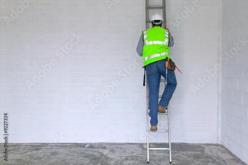 Fotografie, Obraz Workman in reflective vest and hard hat climbing a ladder