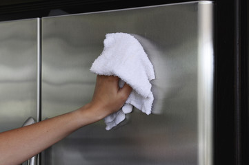 Woman's hand polishing stainless stell fridge