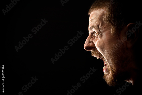 Fotomural Face of angry man screaming isolated on black