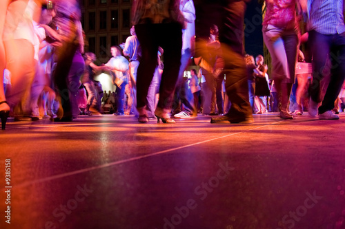 Fotografía  The dance floor with people dancing under the colorful lights.