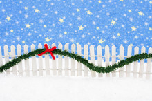 White Picket Fence With Green Garland And Red Bow