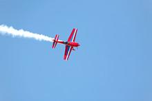 Aerial Acrobatics - Red Propeller Plane With Smoke Blue Sky