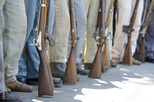 Leinwand Poster Civil War re-enactors  with period guns stand in a row.