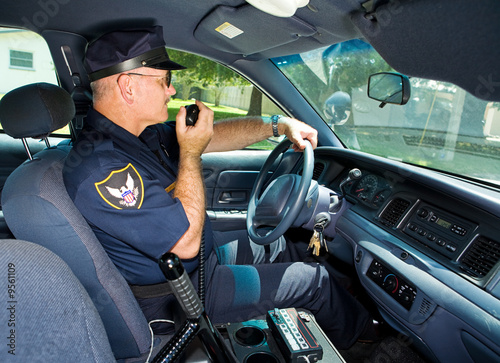 Fényképezés  Police officer in his squad car, talking on his radio.