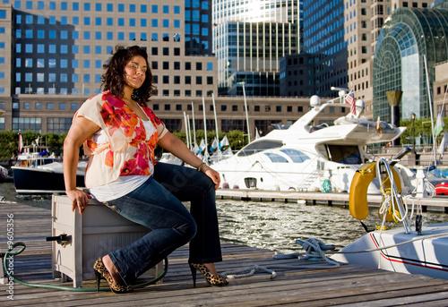 Photo  Beautiful plus size woman sitting at a marina dock
