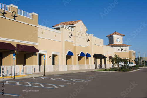 Fotografía  upscale pastel strip mall with awnings and corner clock tower
