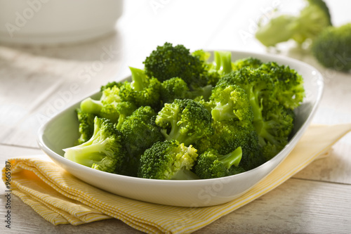 Photo  boiled broccoli in white bowl on table