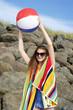 canvas print picture - Pretty brunette at beach holding a beach ball
