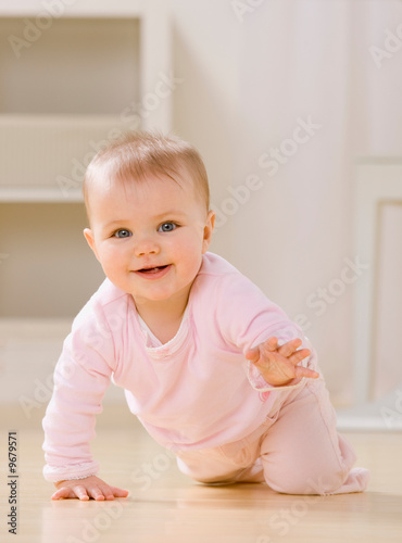 Fotografie, Obraz  Close up of smiling baby crawling on livingroom floor