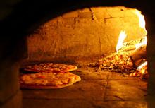 Pizzas Baking In An Open Firew...