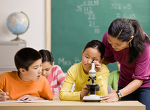 Student Peering Through Microscope In Science Classroom