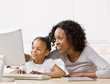 canvas print picture - Devoted mother helping girl do homework on computer