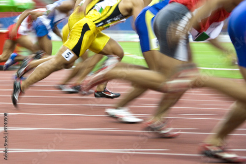 Photo 100 meters athletes in action with intentional blurring.