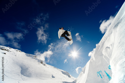 1c58f45936e Photo Snowboarder jumping through the air with blue sky background