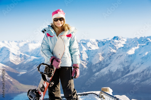 Fotografie, Obraz  Woman holding snowboard with mountains in background