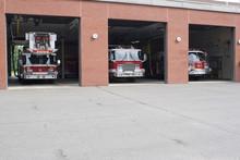 Three Garage Bays Of Fire House Open With Firetrucks
