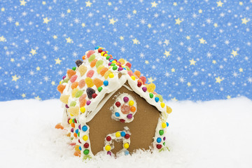 Gingerbread house on snow with star background