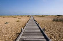 A Raised Wooden Boardwalk Across A Pebble Beach