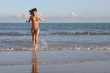 Shapely young female running out of the sea